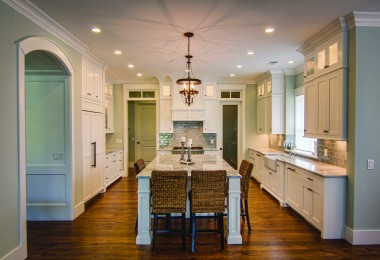 The wood floors and white cabinets in the large, bright kitchen are all naturally lit by a well placed window.