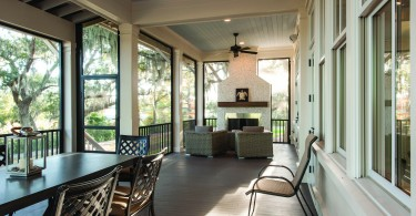 A furnished sunroom with wood floors, large windows, and a white and brown color scheme