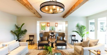 A large, open living room with lots of seating, a round wooden table, and plants
