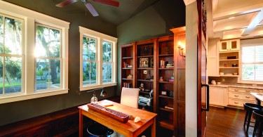 a nook in a home with wood floors, a desk, and wooden shelves. Lots of functional storage space.